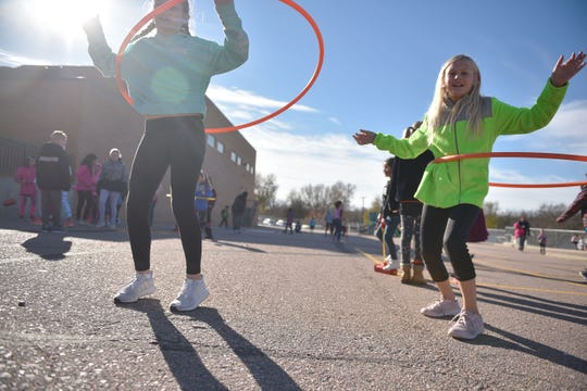 """Eugene Field fourth-graders Katie Condron, left, and Sophie DeBoer, right, do the Hula hoop during recess at school Wednesday, Oct. 31, in Sioux Falls. The school brings out different activities for students to do each day as part of a new 'recess for all"""" concept."""