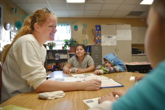 Terry Redlin third grade teacher Chelsea Johnson works with Amy Barillas Barrera, center, Deven Comer, right, and Tatyianan White Buffalo, far right, during class Wednesday, Oct. 31, in Sioux Falls.