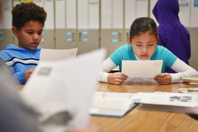 Terry Redlin third grade students Austin Smith, left, and Tatyiana White Buffalo, right, read a short story during class Wednesday, Oct. 31, in Sioux Falls.