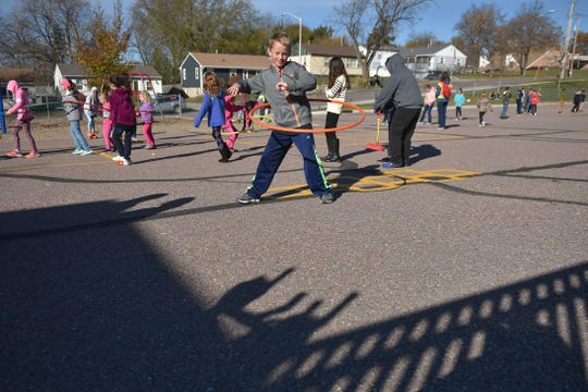 Eugene Field student Porter Altena does the hula hoop during recess at school Wednesday, Oct. 31, in Sioux Falls. The school brings out different activities for students to do each day.