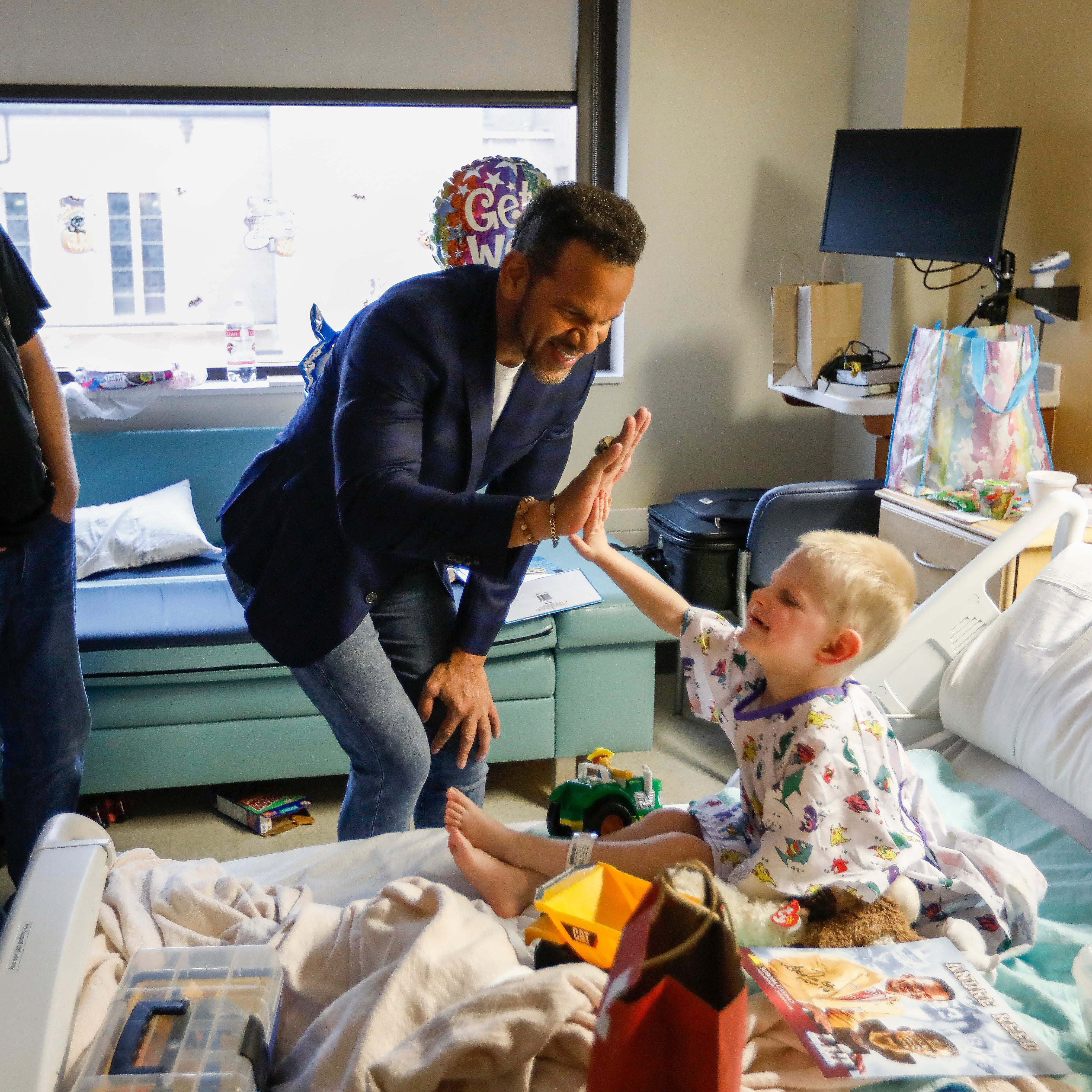 NFL Hall of Fame wide receiver Andre Reed high-fives Elijah Miller, 4, of Purdy, who was in the hospital with encephalopathy, at Mercy Hospital on Wednesday, Oct. 31, 2018.