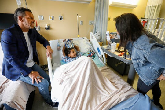 Romin Boyle, 6, of Bentonville, who was in the hospital because of a ruptured appendix, watches a video of NFL Hall of Fame wide receiver Andre Reed, left, on a cellphone held by Theresa Villano at Mercy Hospital on Wednesday, Oct. 31, 2018.