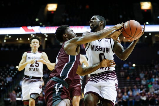 Missouri State senior Josh Webster looks for an open teammate as Evangel senior Jaylen Jones attempts to knock the ball free during a game at JQH Arena on Tuesday, Oct. 30, 2018.