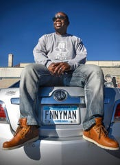 Comedian Adrian Washington poses with his custom license plates Wednesday, Oct. 31, in downtown St. Cloud.