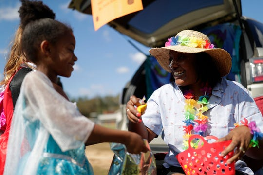 Principal Anicia Robinson hands out candy to Nevaeh Wright, a first grader, during trunk or treat at Sabal Palm Elementary in Tallahassee, Fla. Tuesday, Oct. 30, 2018.