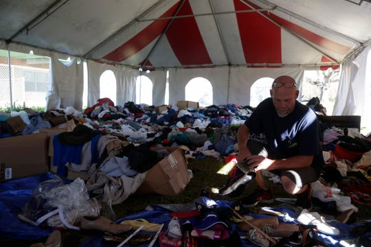 Wewahitchka resident Buddy Simmons, who lost his home in Hurricane Michael, searches for clothes and shoes for his wife and grandchild in a tent filled with donations for victims of the storm along North Second Street in Wewahitchka, Fla. Tuesday, Oct. 30, 2018, three weeks after the storm devastated the community.