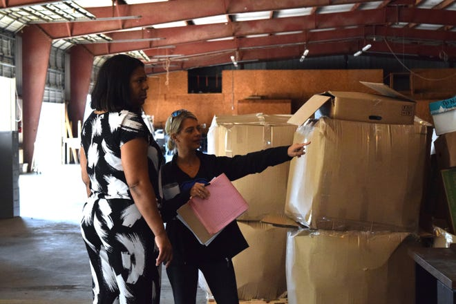 Griffin Middle School Principal Zelena O'Banner (left) and Assistant Principal Brooke Brunner survey potential items that they'll take back to the school from a TCC warehouse.