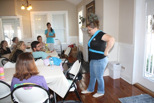Nancy Fry of Baby K'tan® demonstrates how the baby carrier is worn at a Babywearing Basics class held recently at the newly opened Bell House Birth Services in Stuart.