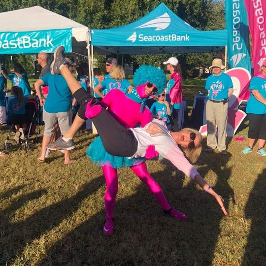 """Emcee Tiffany Kenney and """"Pink Man"""" Kevin Davis, from Presenting Sponsor Seacoast Bank, have some fun at the 2018 Making Strides Against Breast Cancer walk in Stuart."""