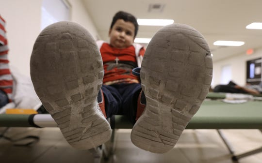 Brathley Galindo, 6, rests on at cot at a Catholic Diocese of El Paso shelter, showing shoes worn during a long journey from Guatemala.