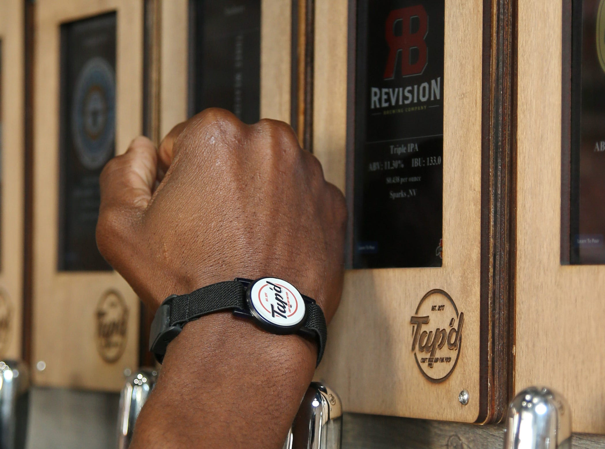 Robert Washington, CEO and co-owner of Tap'd Ventura, demonstrates how the business' patrons activate self-serve taps with the use of an RIFD wristband. The combination taproom and restaurant offers beer, wine and hard ciders and kombuchas on 43 taps.