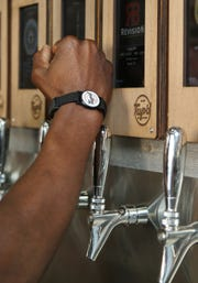 Robert Washington, CEO and co-owner of Tap'd Ventura, demonstrates how the business' patrons activate self-serve taps with the use of an RFID wristband.