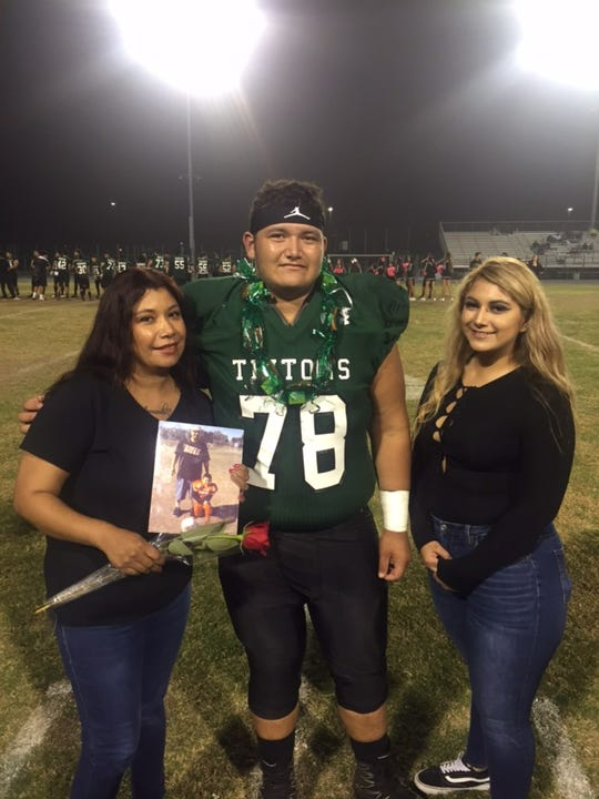 Pacifica High senior Armando Sifuentes poses with his mother Ysenia and sister Amanda during the Tritons' Senior Night last week.