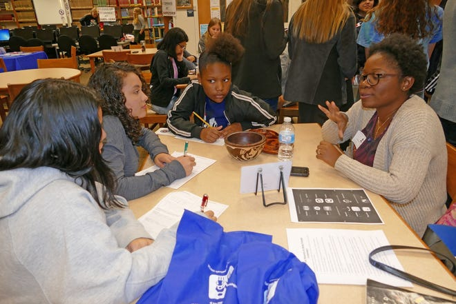 Stephanie Jean-Joseph (right) of the South Jersey Family Medical Center speaks with students at Cumberland Regional High School's World Language Fair.