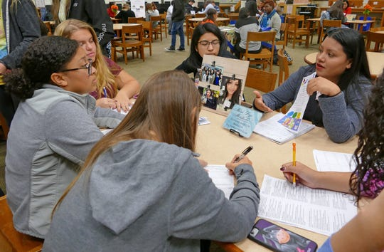 Maria Trejo-Mendiola (right) of Pathstone Agency of Bridgeton speaks with students at Cumberland Regional High School's World Language Fair.
