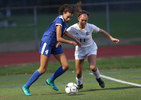 From left, Bronxville's Catherine Faville (4) and O'Neill's Alyssa Hill (11)  battle for ball control in the Class B regional girls soccer semifinal at Arlington High School in Freedom Plains Oct. 31, 2018. Bronxville won the game 2-0.