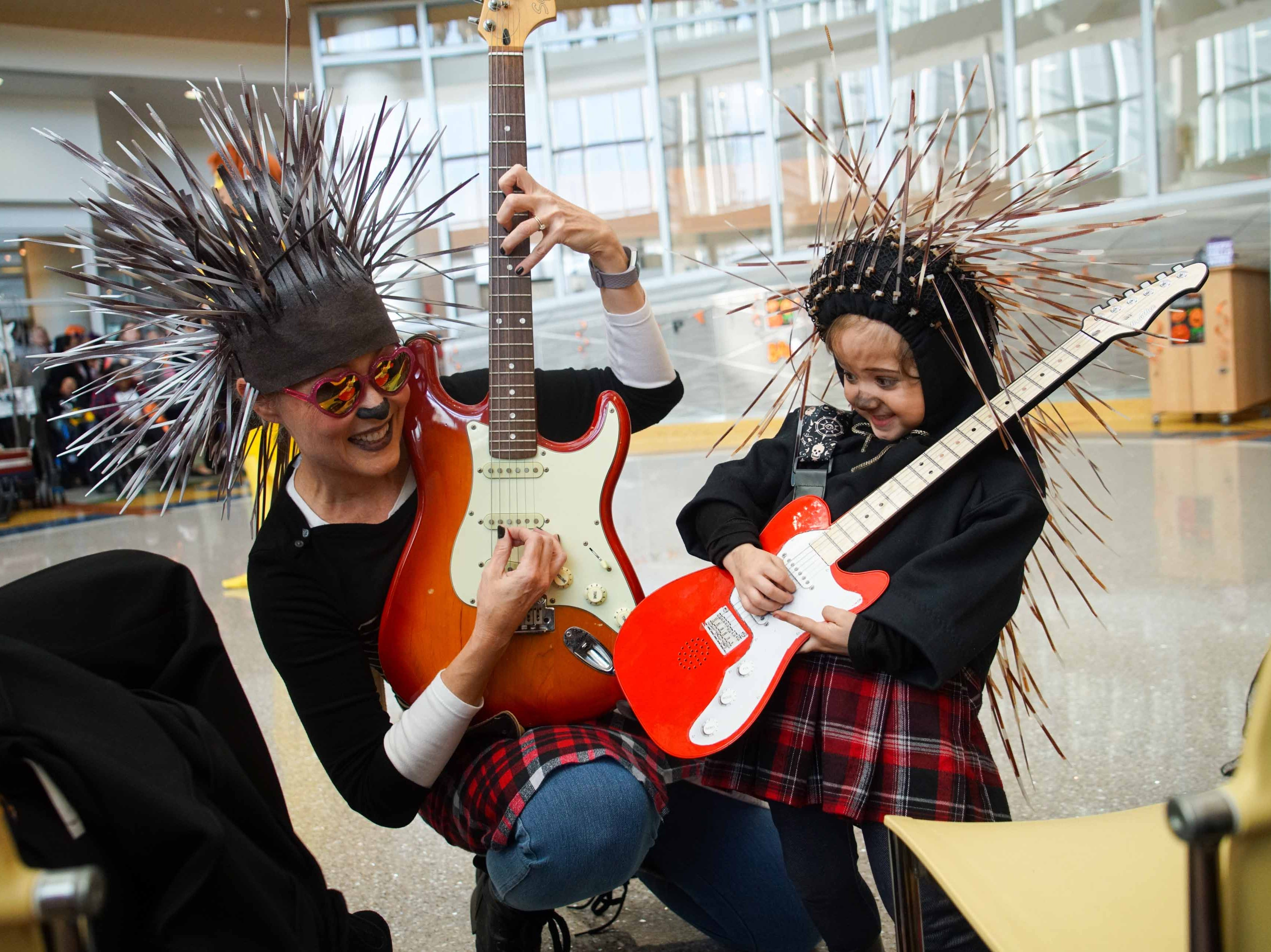 """(left to right)Dr. Sharon Gould, at Nemours/A.I. duPont Hospital for Children, plays guitar with Penelope O'Grady, 4, who both came dressed as the character Ash from the movie """"Sing"""" for the annual Halloween Lip Sync contest in the hospital's atrium on Halloween."""