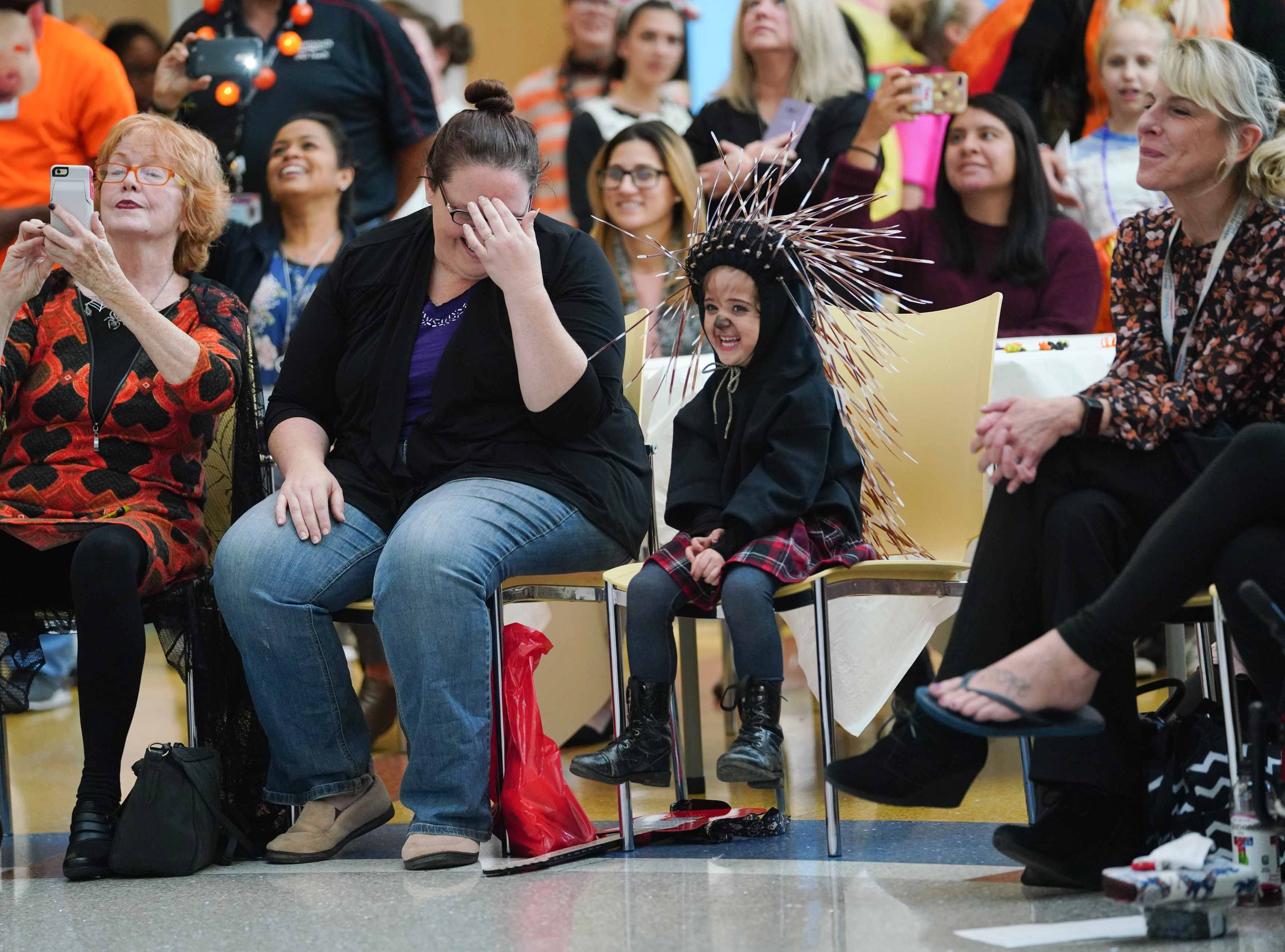 """(left to right)Eileen Wellman takes a photograph of staff members at Nemours/A.I. duPont Hospital for Children as they dressed in costume to entertain patients and family at the annual Halloween Lip Sync contest in the hospital's atrium on Halloween. Kimberly O'Grady laughs next her daughter Penelope, 4, who dressed at Ash from the movie """"Sing""""."""