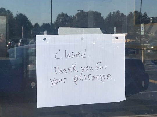 A handwritten sign on the door of Gooey Donuts says the business has closed.