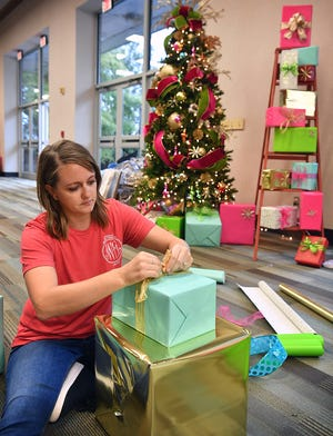 Junior League member Lauren Wuthrich wraps decorative gift boxes while helping set up for the 37th Annual Christmas Magic event Wednesday at the Ray Clymer Exhibit Hall. The marketplace is open Friday and Saturday 9 a.m. to 7 p.m. and Sunday from Noon to 5 p.m.