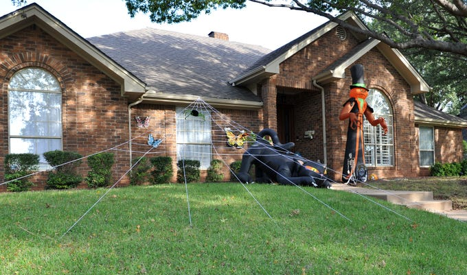 A home in Tanglewood is decorated with a large spider, an inflatable black cat and a large ghoul for Halloween.