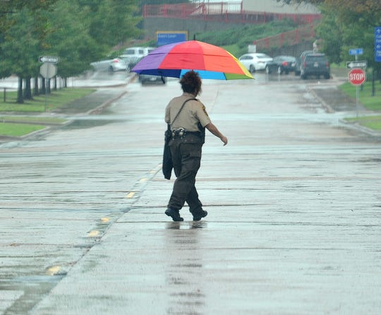 A pedestrian uses an umbrella to shield against the rain while walking near downtown Wichita Falls Wednesday morning. Wichita Falls residents saw a wet morning as rain covered most of the city.