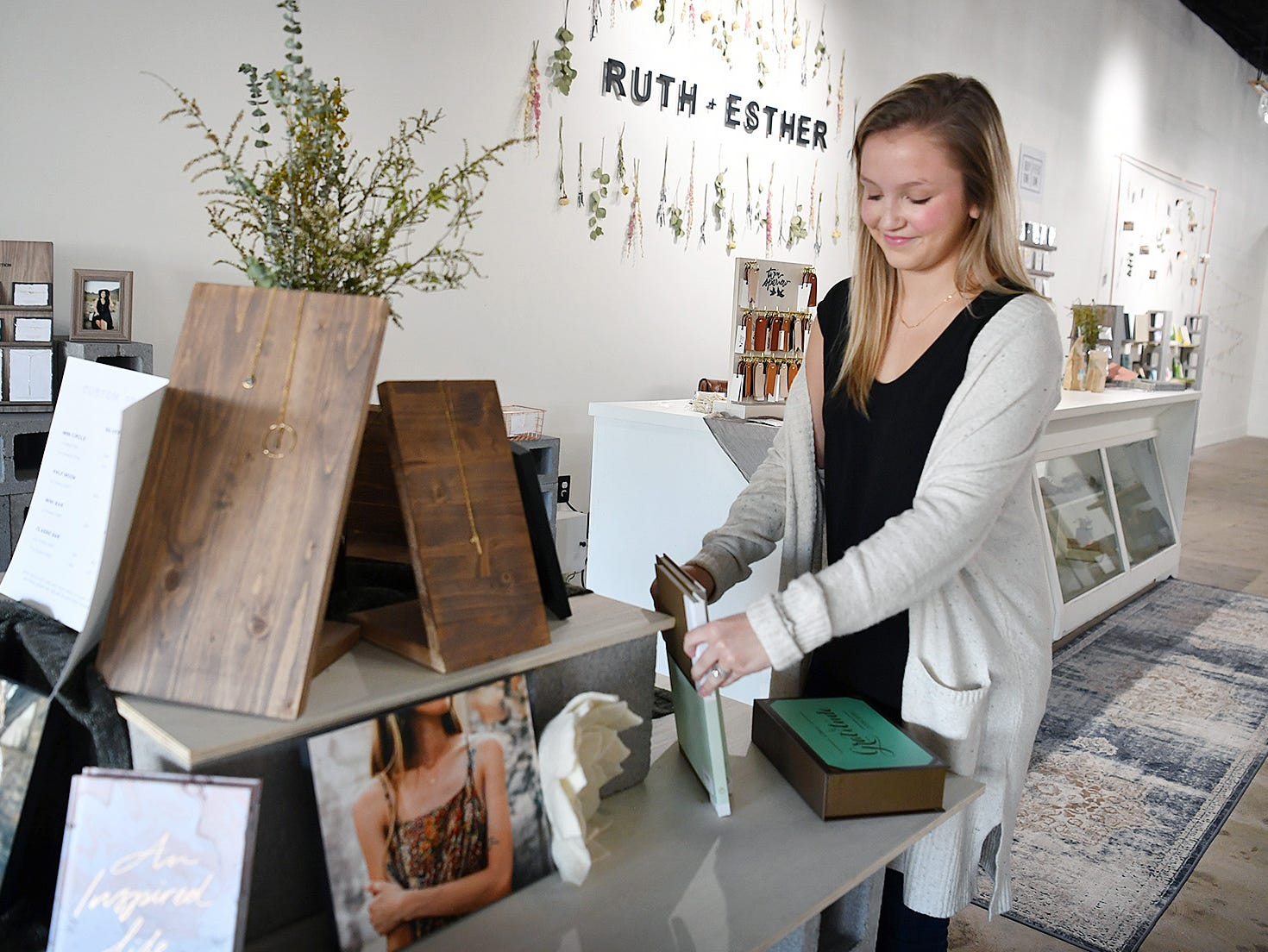 Creative Director Lauren Foster sets up merchandise in the new Ruth & Esther store in Scott Square. The business is a division of Dear Heart, a jewelry business started by Nichole Kirk in 2013.