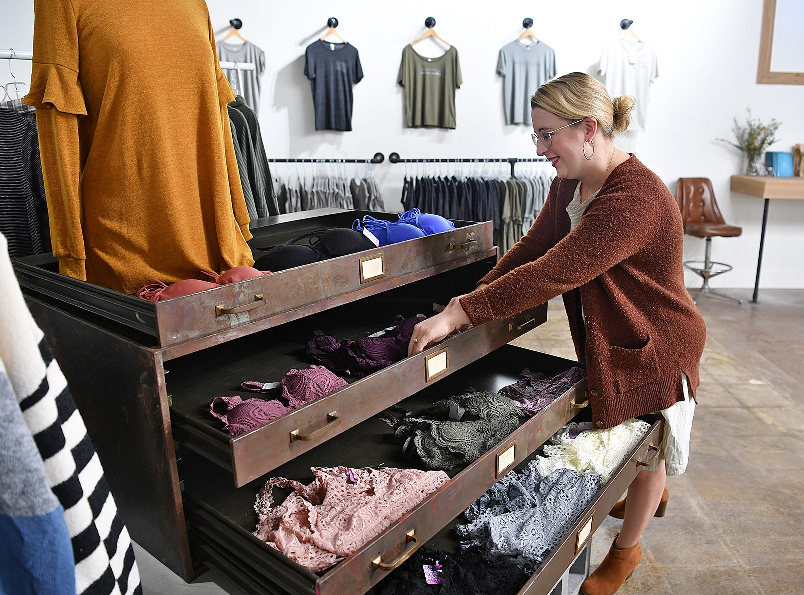 Holly Levell, a creative director at Ruth & Esthers, sets up a display in the apparrel area of the store that opened in August.