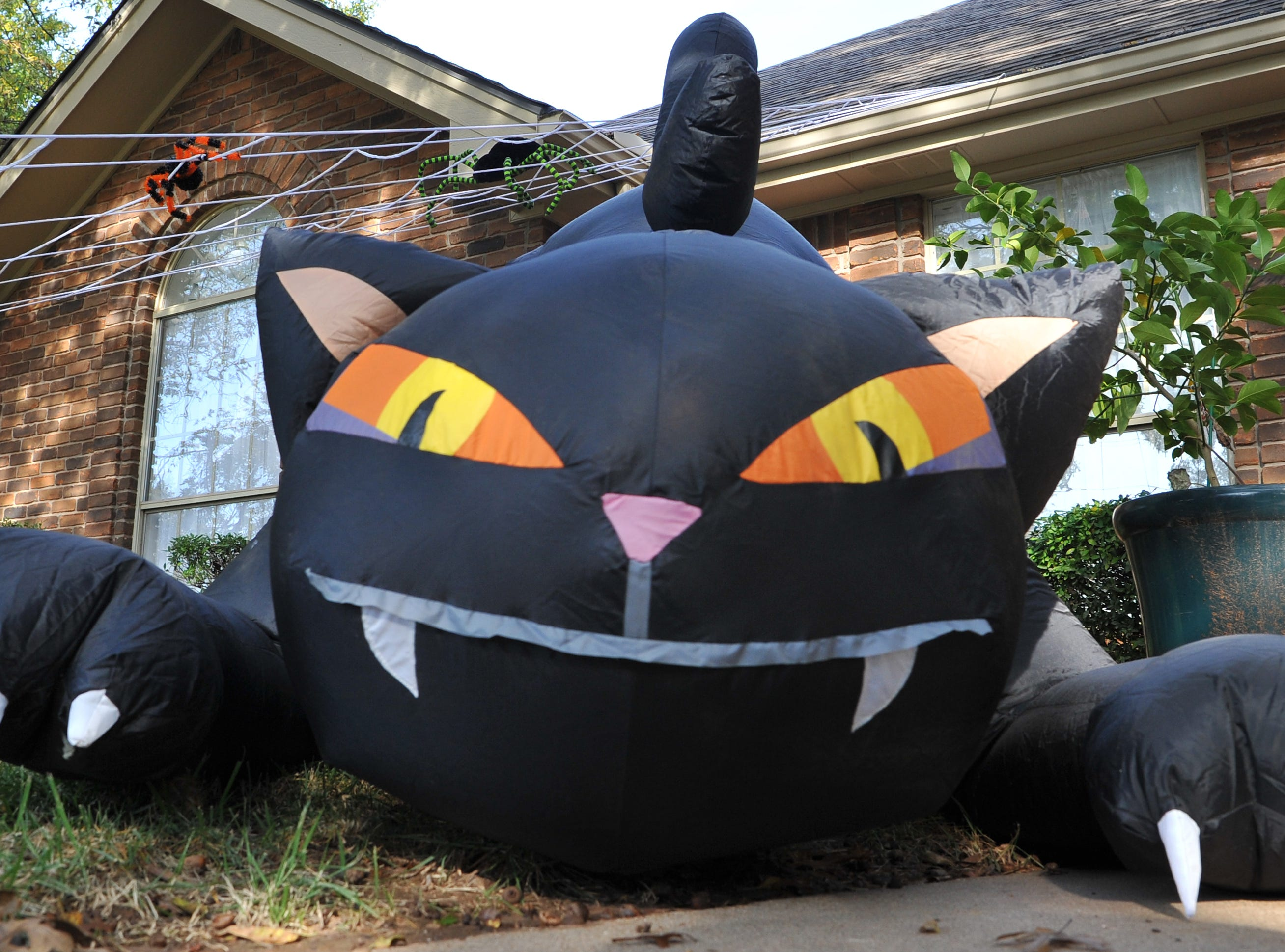 A home in Tanglewood is decorated with a large inflatable black cat for Halloween.