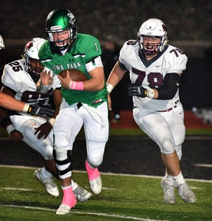 Vernon defenders A.J. Moore (25) and Marc Rodriguez (78) close in on Iowa Park quarterback Trent Green during their game in Iowa Park October 19.
