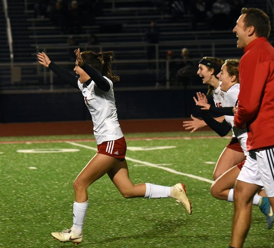 Parker Farrell leads the charge towards Kailey Zemba after she scored the winning goal against Grandview Heights in a shootout during Tuesday night's regional semifinal at Lakewood High School.