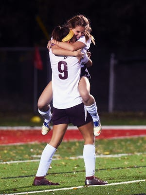 Gabby Lemon, left, hugs teammate Sarah Bennett after John Glenn earned a 1-0 shootout win against River View in a Division II regional semifinal match on Tuesday at Stewart Field in Coshocton. It marked the program's first regional victory.