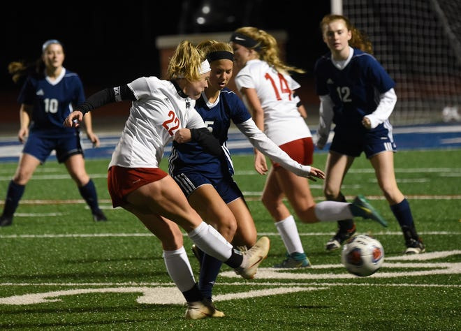 Bishop Rosecrans' Claire Creeks passes the ball against defense from Grandview Heights' Lindsey Bertani during Tuesday night's regional semifinal at Lakewood High School. Rosecrans won in a shootout to earn a 2-1 win over the Bobcats.