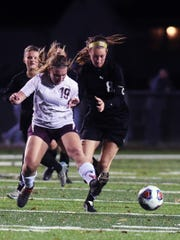 Cora Wilkins, left, and Emmie Brenly chase the ball during John Glenn's 1-0 shootout win in a Division II regional semifinal on Tuesday night at Stewart Field in Coshocton.