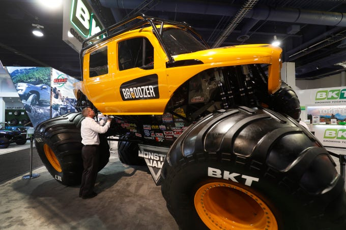 A man looks over the Brodozer, a diesel monster truck, on display at the BKT booth during SEMA.