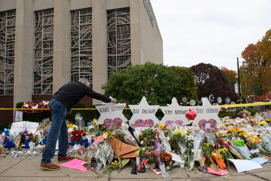 Mourners visit the memorial outside the Tree of Life Synagogue on Oct. 31 in Pittsburgh. Eleven people were killed in a mass shooting.