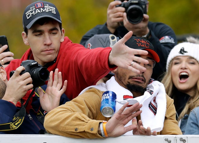 A Boston Red Sox staff member, left, tries to keep a tossed beer can from hitting outfielder Mookie Betts during the team's World Series championship parade.
