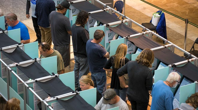 People cast their votes on the third day of early voting at the Galleria at Sunset in Henderson, Nev. on Oct. 22, 2018.
