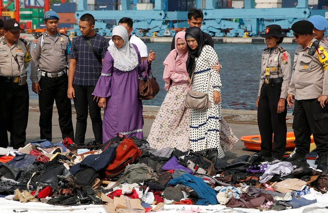 The wife of a police officer who was aboard the crashed Lion Air plane looks for her husband's belongings at the collection point at Tanjung Priok Harbour, Jakarta, Indonesia, 31 October 2018.