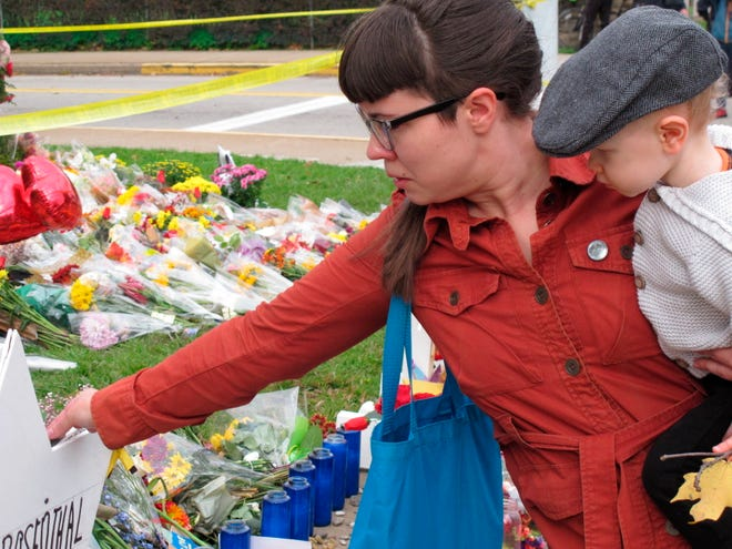 Kathleen Fuller, holding her son Garrick, places a stone on a Star of David at a memorial in front of Tree of Life synagogue in Pittsburgh on Oct. 31, 2018.