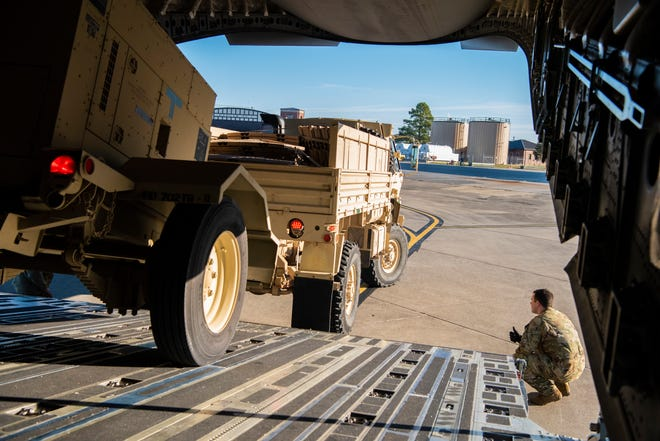 "In this photo provided by the U.S. Air Force, Airman 1st Class Trevor Pearce helps guide a military vehicle into the cargo compartment of a C-17 Globemaster III at Fort Knox, Ken., on Oct. 29, 2018, as the aircrew prepares to deploy to the southwest border in support of ""Operation Faithful Patriot."""