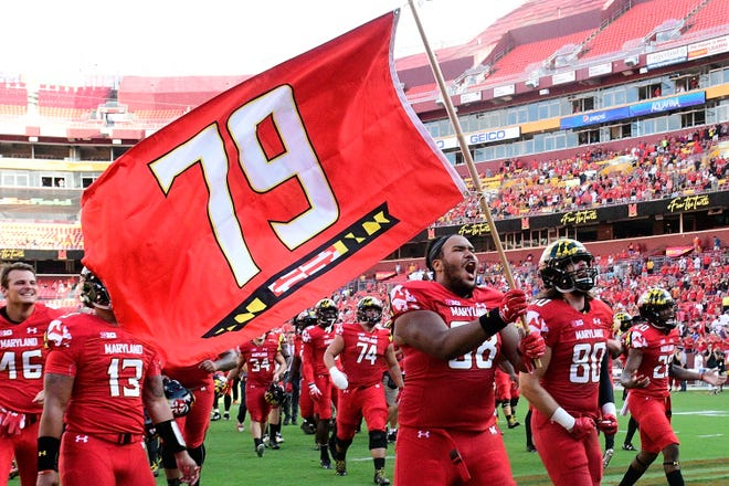 Maryland offensive lineman Ellis McKennie runs onto the field with his teammates holding a flag in remembrance of Jordan McNair on Sept. 1 at FedEx Field in Washington, D.C.