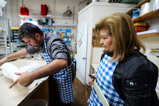 Nina Torres still enjoys decorating cakes after more than 26 years in business as owner of Cakes Plus in Tampa, Florida. Her son Mario Torres, shown rolling out  homemade fondant for a cake, serves as her pastry chef.