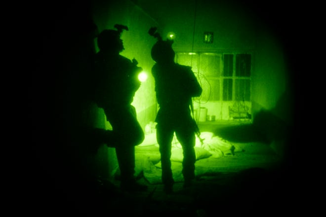 In this Oct. 28, 2009 file photo taken with a night vision scope, U.S. Special Operations forces search a home during a joint operation with Afghan National Army soldiers targeting insurgents operating in Afghanistan's Farah province.