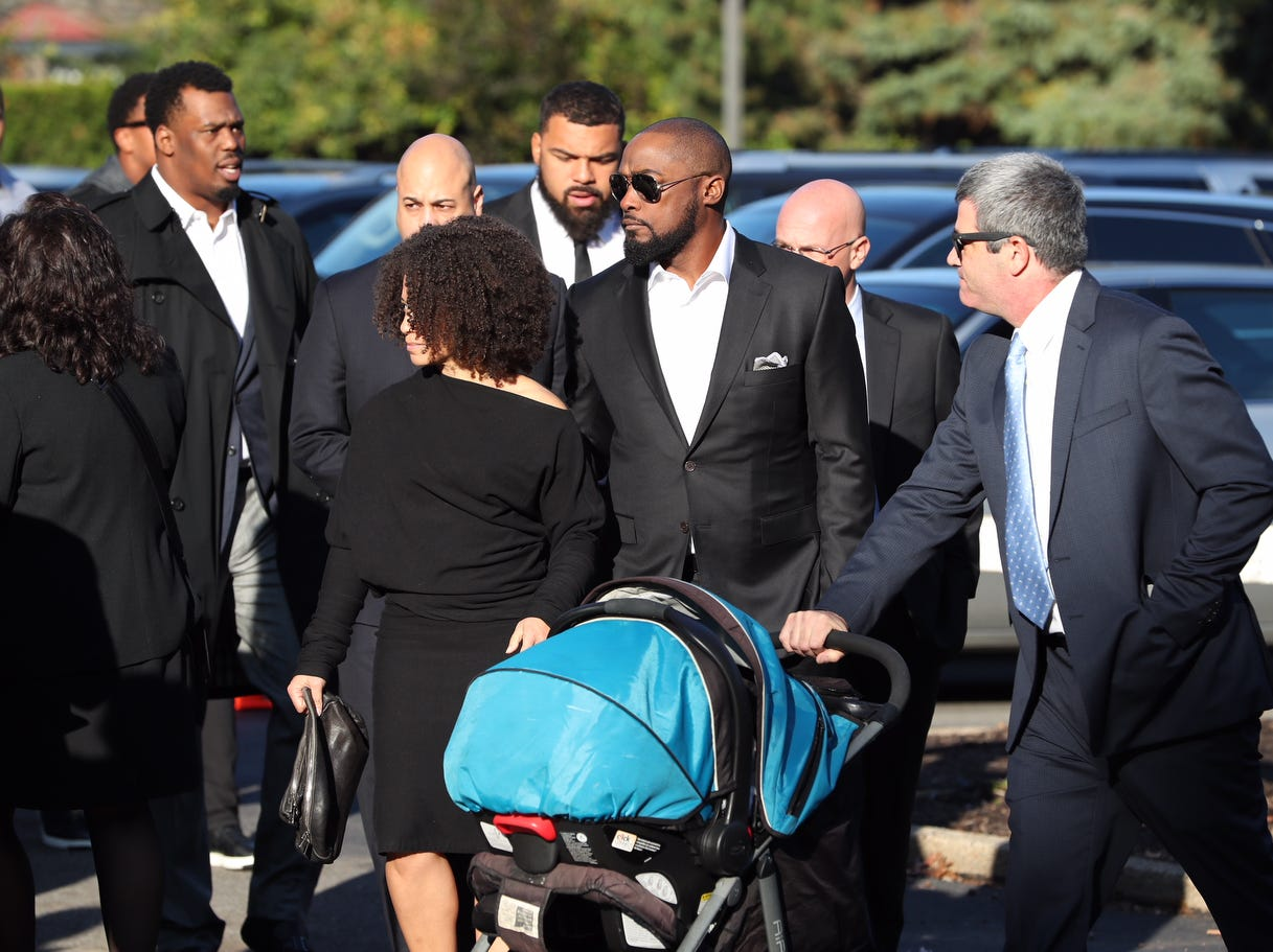 Pittsburgh Steelers football coach Mike Tomlin, center, and Cameron Heyward, behind, arrive at the funeral for brothers David and Cecil Rosenthal at the Rodef Shalom Congregation.