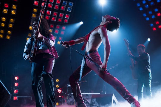 "Queen bandmates Brian May (Gwilym Lee, left), Freddie Mercury (Rami Malek) and John Deacon (Joe Mazzello) perform in one of the many concert sequences in ""Bohemian Rhapsody."""