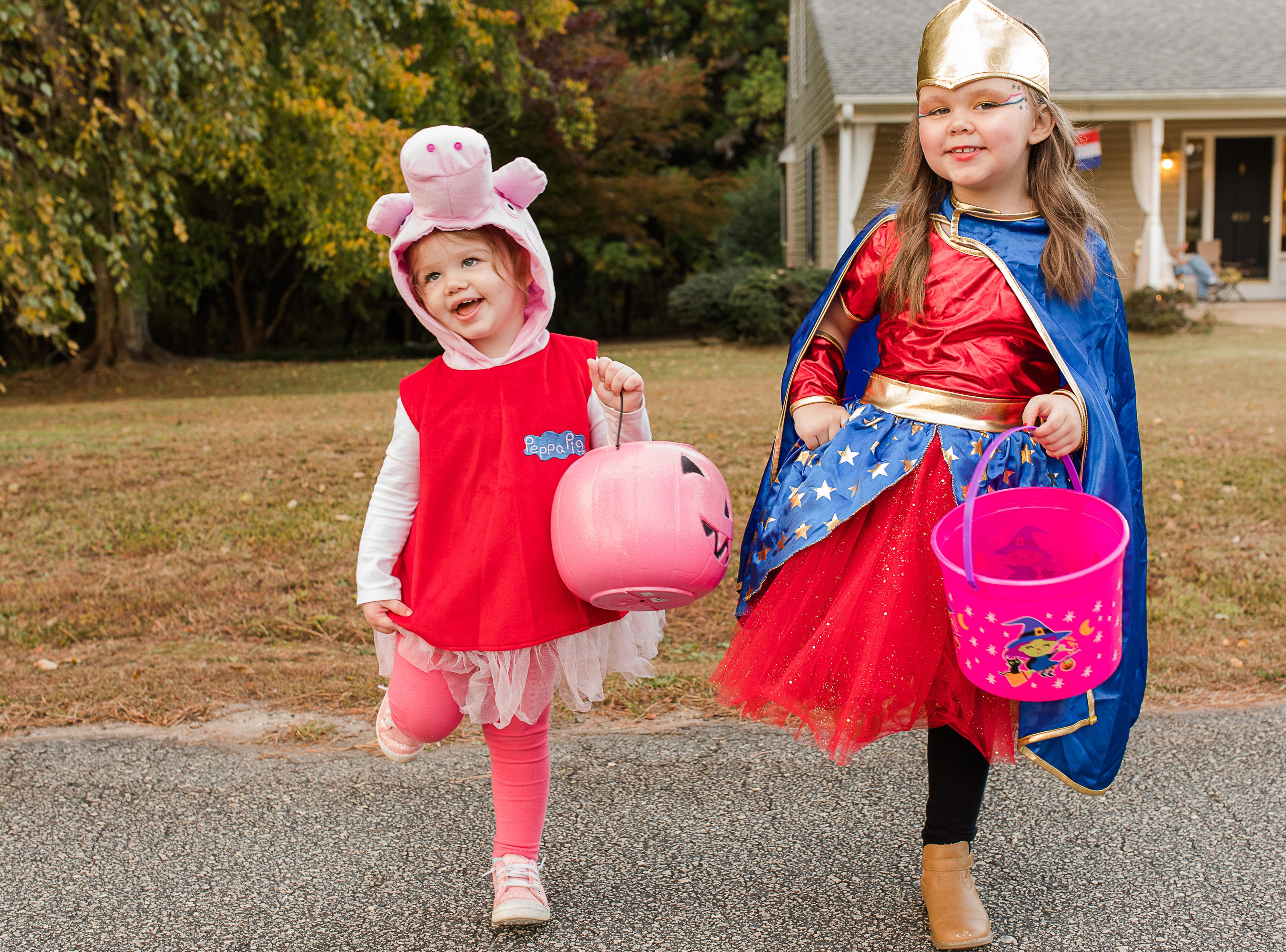 Two year old Lila and four year old Audrie Harbin enjoy trick-or-treating in the Cobb's Glenn subdivision in Anderson Wednesday, October 31, 2018.