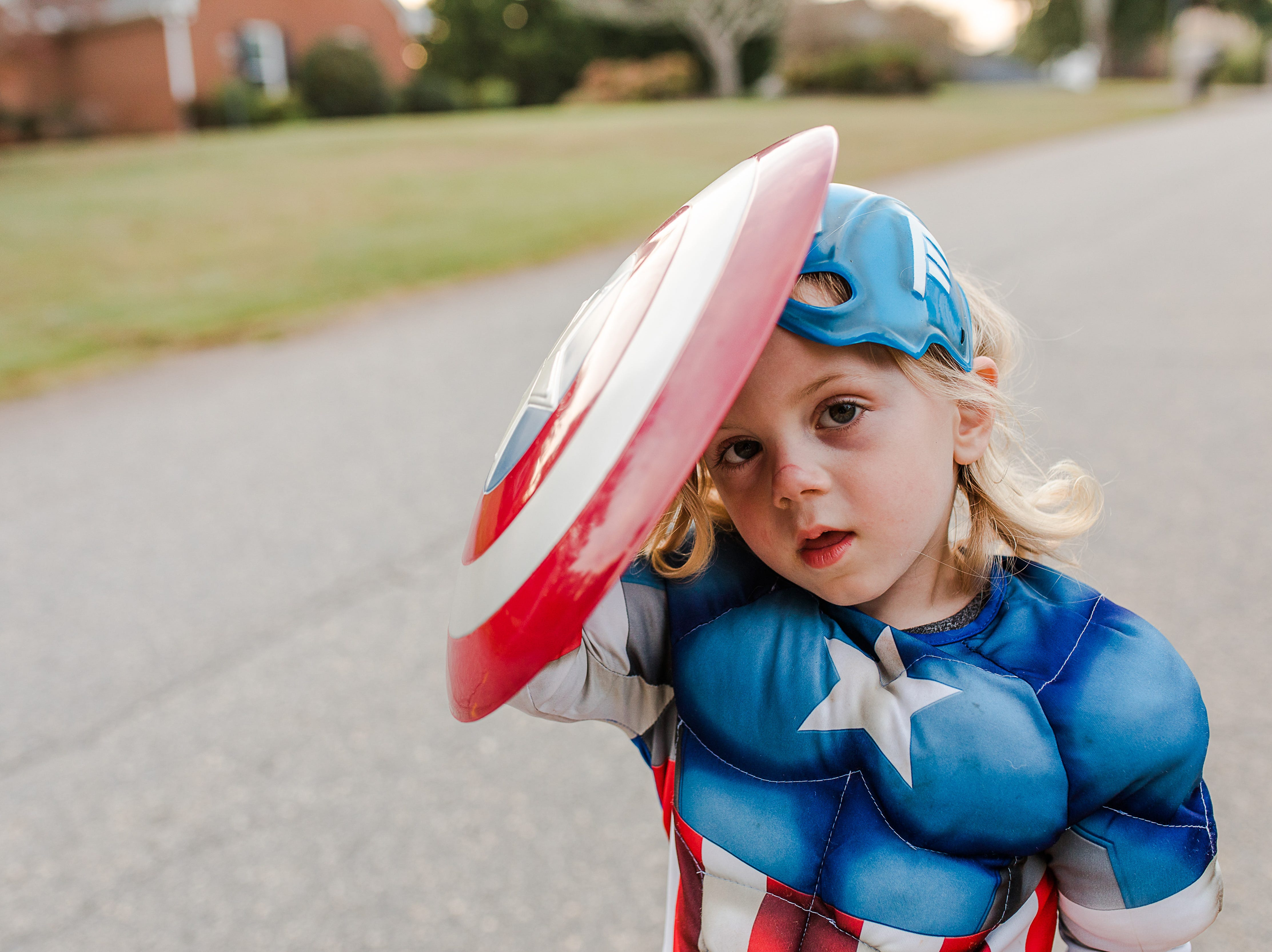 Three-year-old Everett Durkin uses his shield  while trick-or-treating in the Cobb's Glenn subdivision in Anderson Wednesday, October 31, 2018.