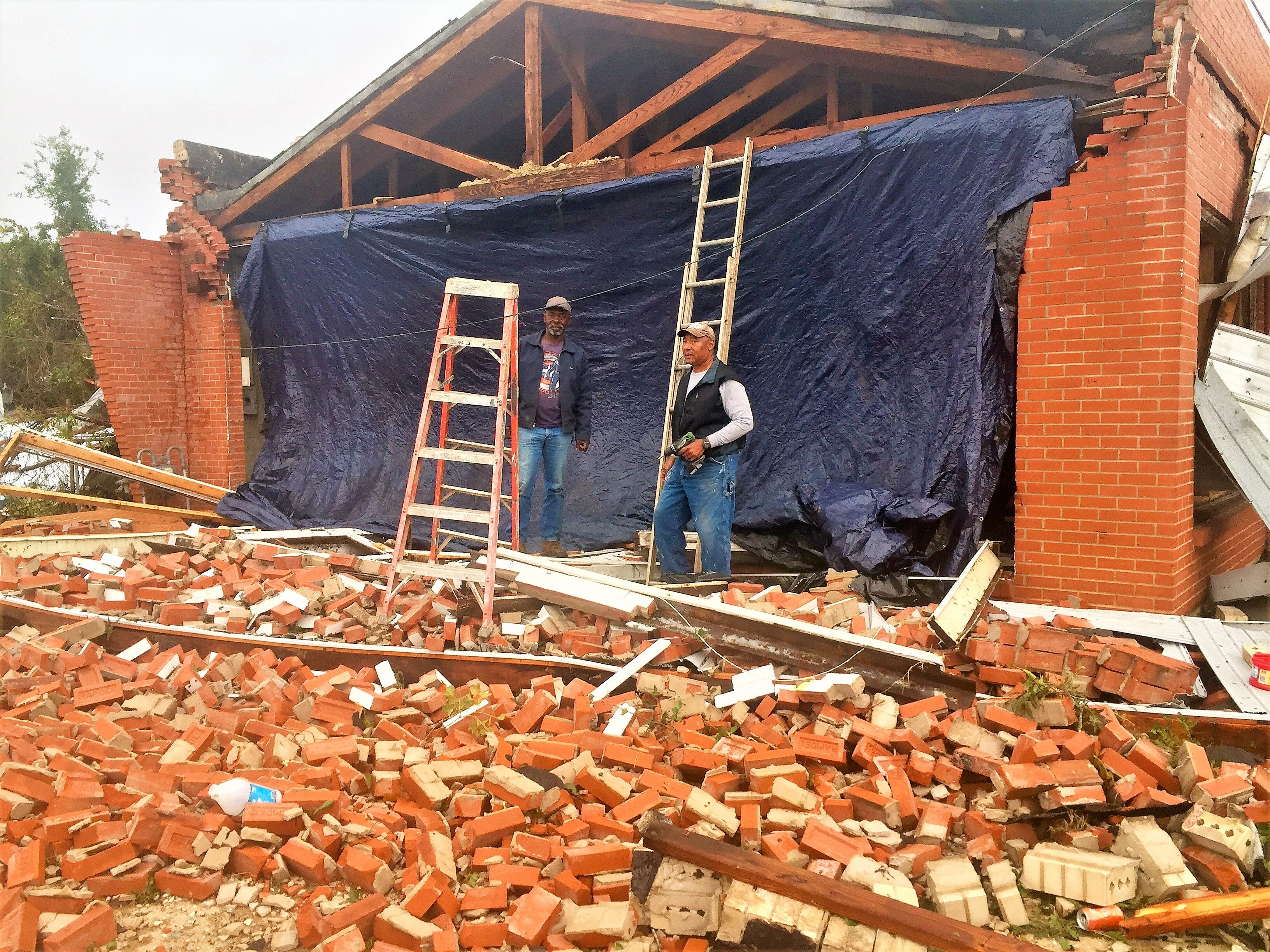 Lemroy Culbert (right) and David Doyle work to protect Culbert's building on Lee Street in Alexandria from the elements on Thursday morning. It was one of several in that area to sustain heavy damage in Wednesday night's storms.