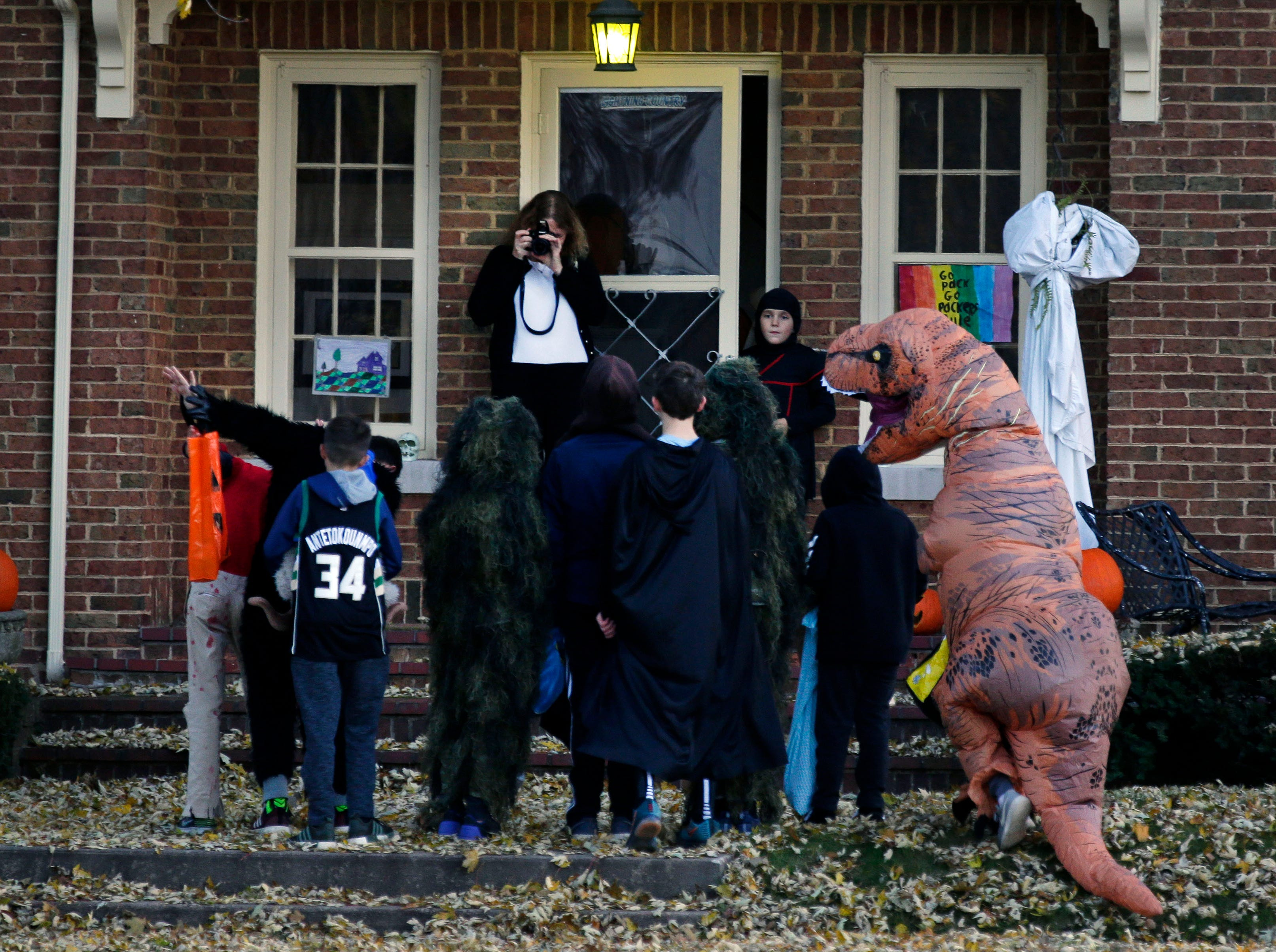 Laura Biskupic gets a photo of trick-or-treaters Wednesday, October 31, 2018, in Appleton, Wis.